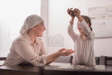 happy cute little child with sick grandmother in kerchief playing with jigsaw puzzle together