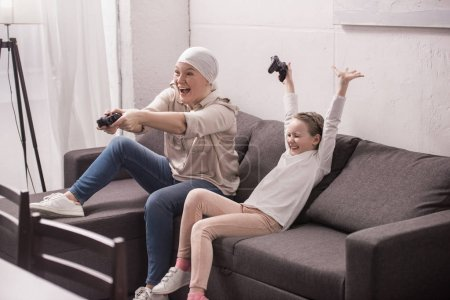 cheerful grandmother and granddaughter playing with joysticks, cancer concept