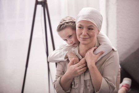 cute little child hugging sick grandmother in kerchief
