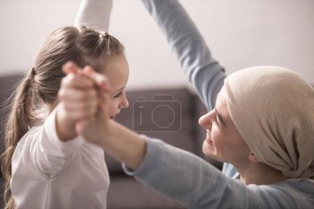 happy child and sick mother in kerchief holding hands and smiling each other