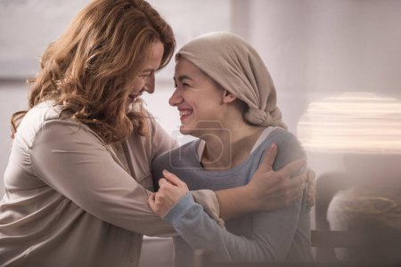 Photo for Happy mother and sick adult daughter in kerchief hugging and looking at each other - Royalty Free Image