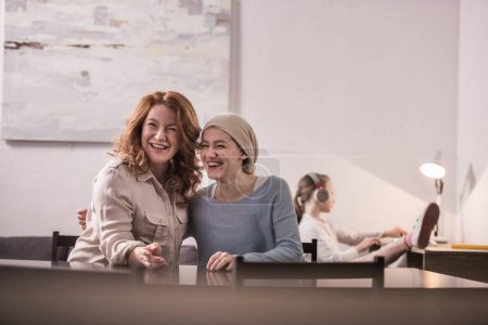 happy mother and sick adult daughter in kerchief laughing while sitting together