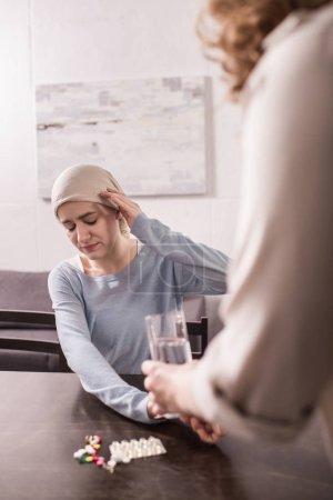 Photo pour Photo recadrée de femme portant le verre d'eau et de la médecine à une fille adulte malade en foulard - image libre de droit