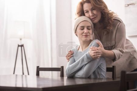 mature woman hugging and supporting sick smiling daughter in kerchief