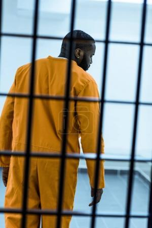 rear view of african american prisoner behind prison bars