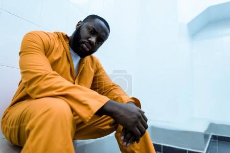 bottom view of african american prisoner sitting on bench and looking at camera
