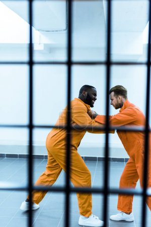 side view of multicultural prisoners threatening each other behind prison bars