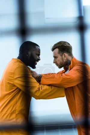side view of multicultural prisoners threatening each other and holding collars