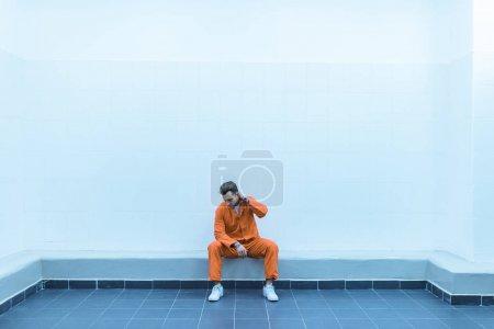 prisoner sitting on bench in prison cell