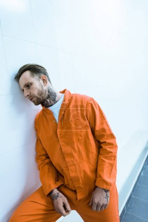 tattooed prisoner leaning on wall in prison cell
