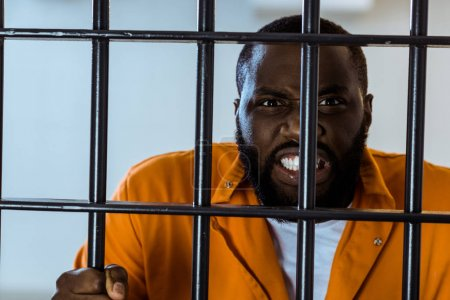 angry african american prisoner holding prison bars