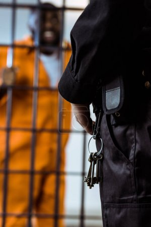 cropped image of prison guard standing near prison bars with keys