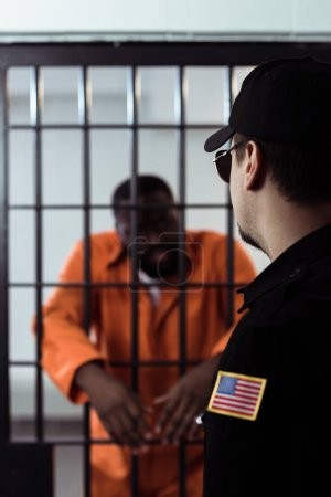 Photo for Security guard standing near prison bars and looking at african american prisoner - Royalty Free Image