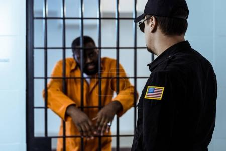 prison officer standing near prison bars and looking at african american prisoner