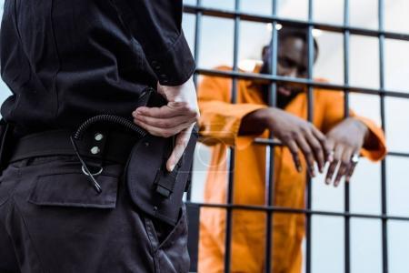 Foto de Recortar imagen de funcionario de prisiones poniendo mano de pistola cerca de barras de la prisión - Imagen libre de derechos