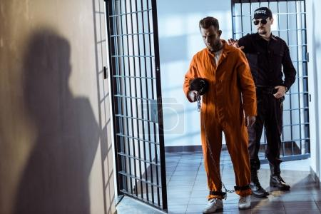 prison warden leading prisoner carrying weight tethered to leg