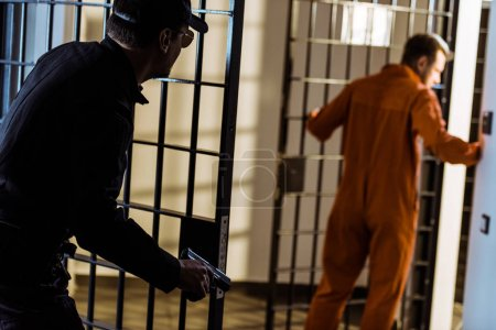 Photo for Police guard pursuing escaping prisoner with gun - Royalty Free Image