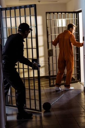 Photo for Police officer pursuing escaping prisoner with gun - Royalty Free Image