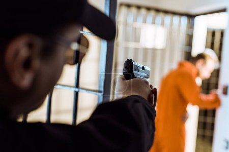 prison officer aiming gun at escaping prisoner