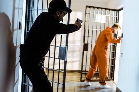 Photo for Prison guard aiming gun at escaping prisoner - Royalty Free Image