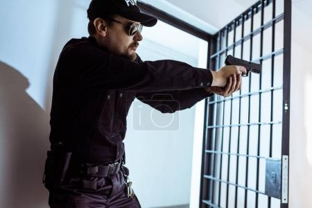Foto de Guardia de la prisión apuntar arma y mirando lejos - Imagen libre de derechos