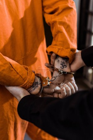 Photo for Cropped image of prison officer holding convict in handcuffs - Royalty Free Image