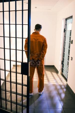 rear view of prisoner standing in handcuffs in corridor