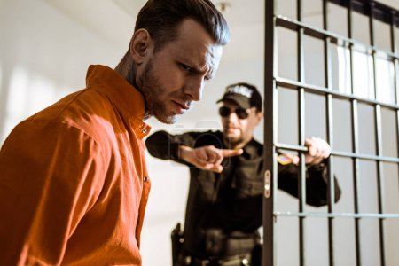 prison guard showing something to criminal in prison cell