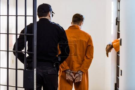Photo for Back view of security guard leading criminal in handcuffs - Royalty Free Image