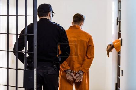 Photo pour Vue arrière du garde de sécurité principal criminel menottes aux poignets - image libre de droit