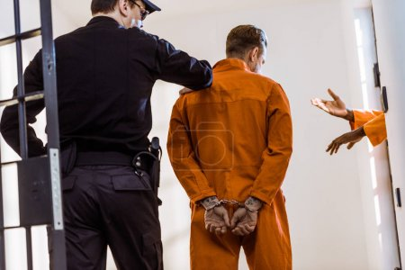 Photo for Back view of prison guard leading criminal in handcuffs - Royalty Free Image