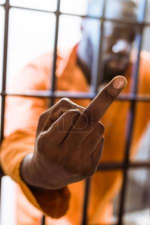 african american prisoner showing middle finger through prison bars
