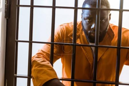 african american prisoner leaning on prison bars and looking at camera
