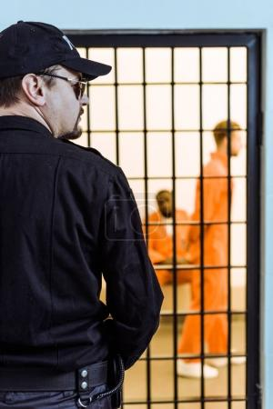 rear view of prison officer standing near prison cell with multicultural inmates