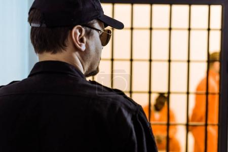 rear view of prison officer standing near prison cell with criminals