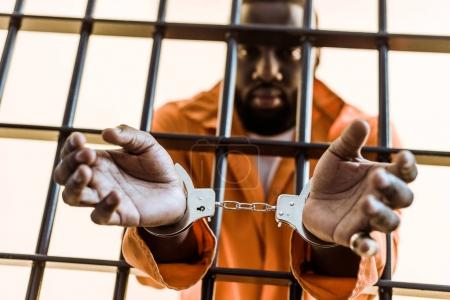african american prisoner in handcuffs behind prison bars