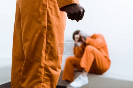 cropped image of african american prisoner standing with fist on foreground