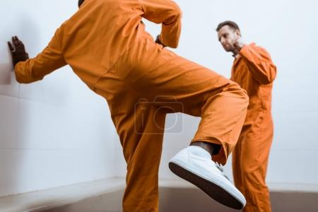 multicultural prisoners fighting in prison cell
