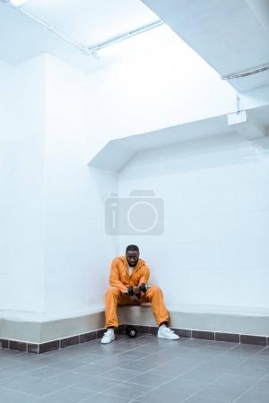 african american prisoner in light modern prison cell