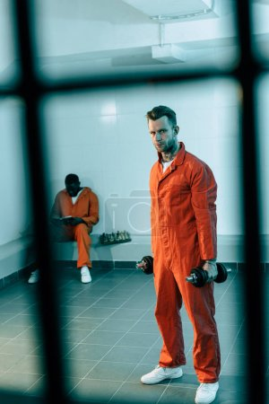 prisoner training with dumbbells in prison room and looking at camera