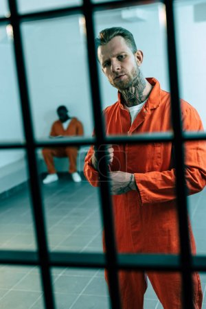 multiethnic criminals in prison cell behind prison bars