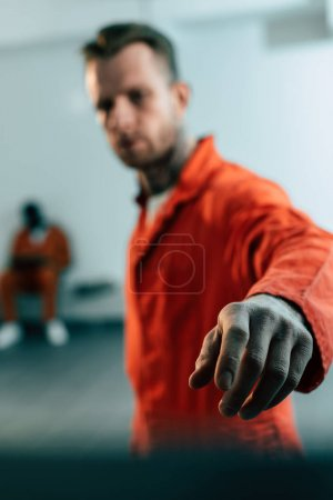 multiethnic prisoners in prison cell with hand on foreground