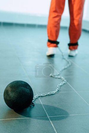cropped image of prisoner in orange uniform with weight tethered to leg
