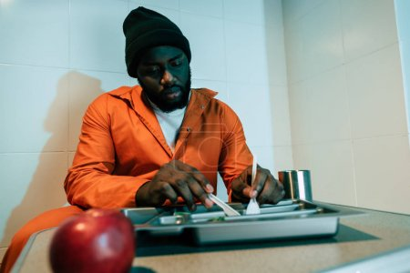 african american inmate eating in prison cell