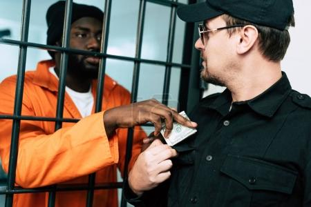 african american prisoner giving money to prison officer as bribe