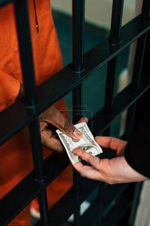 Photo pour Cropped image du prisonnier afro-américain, donner de l'argent au directeur de la prison comme pot de vin - image libre de droit