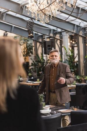selective focus of senior man looking at woman in cafe
