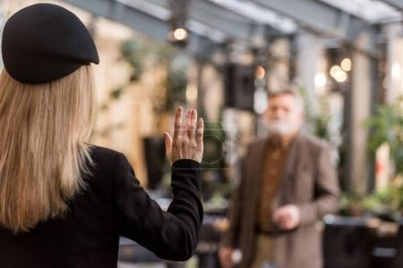 back view of woman waving to man in restaurant