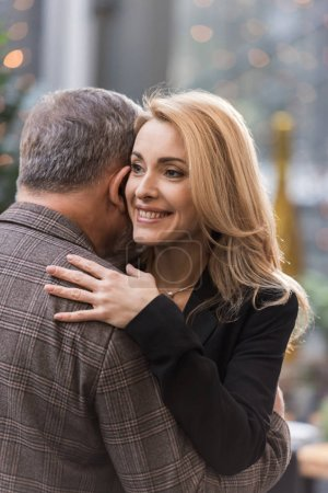 partial view of smiling woman and man hugging each other