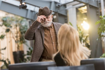 selective focus of senior man in hat looking at woman at table in cafe